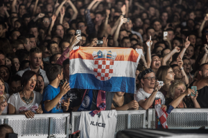 People shouting and cheering while holding flag in Zagreb, Croatia