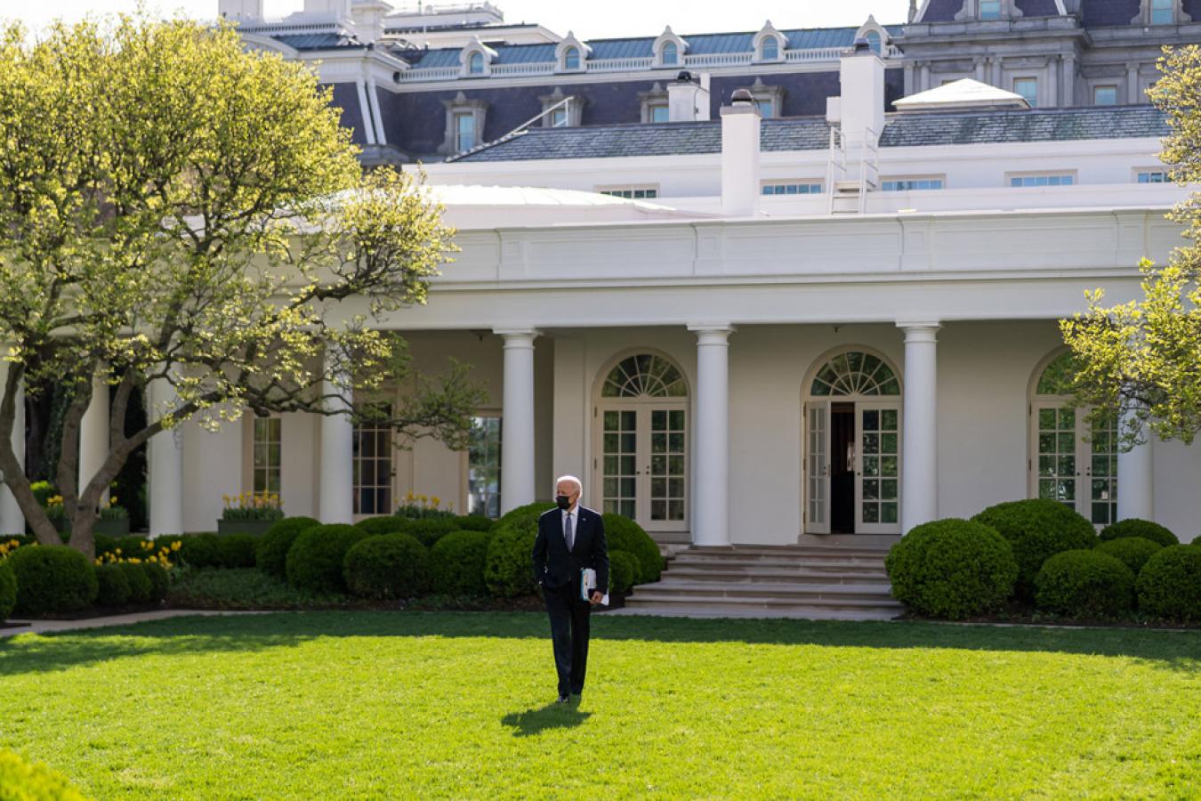 President Joe Biden walks across the Rose Garden of the White House.
