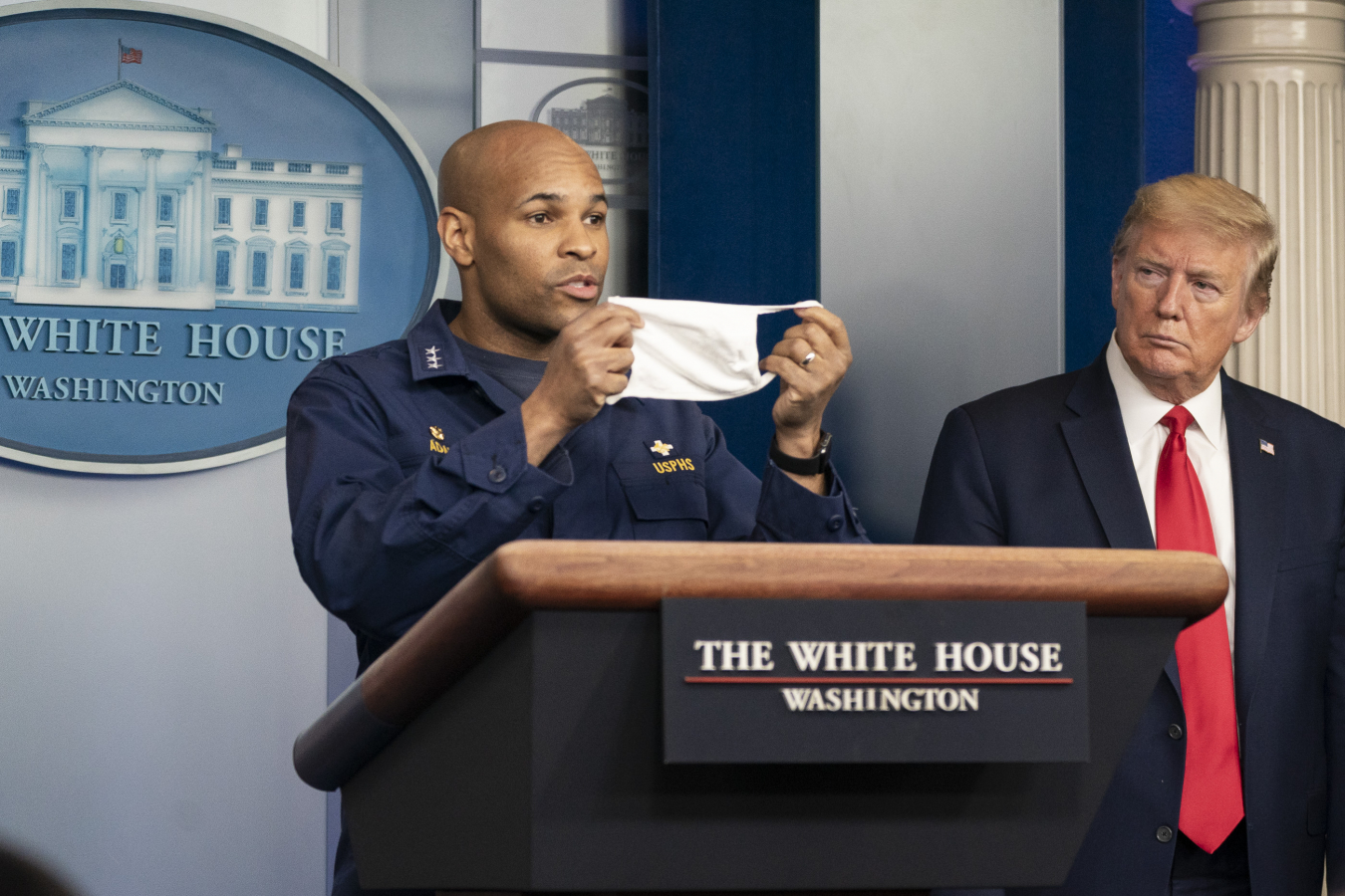 Donald J. Trump listens as U.S. Surgeon General Jerome Adams delivers remarks and urges citizens to wear masks in public at the coronavirus (COVID-19) update briefing Wednesday, April 22, 2020